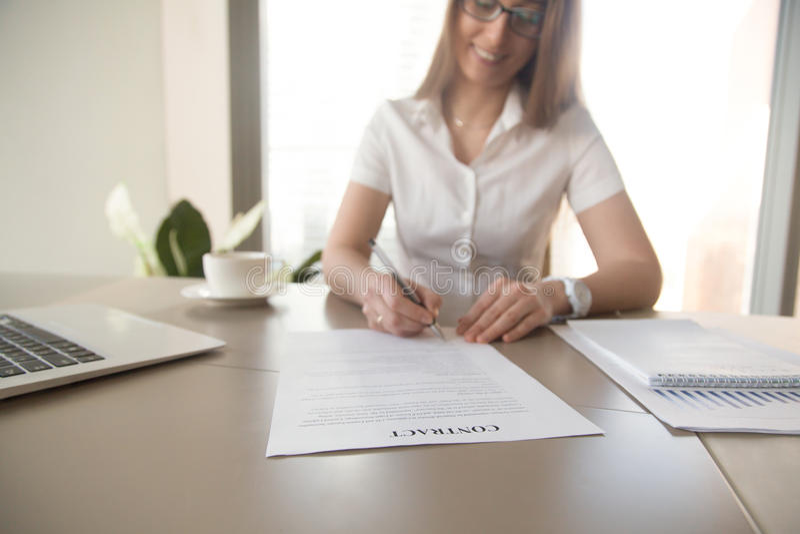 La empresaria sonriente firma un contrato en el escritorio imagenes de archivo