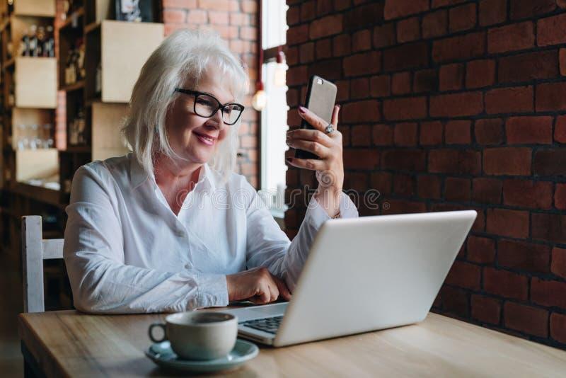 La empresaria sonriente se está sentando en la tabla delante del ordenador portátil y foto de archivo