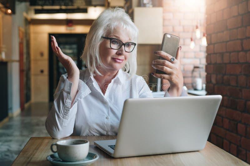 La empresaria sonriente se está sentando en la tabla delante del ordenador portátil y la mirada de la pantalla del smartphone en  foto de archivo