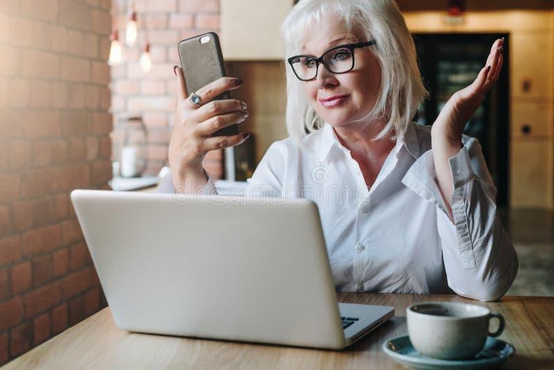 La empresaria sonriente se está sentando en la tabla delante del ordenador portátil y la mirada de la pantalla del smartphone en  foto de archivo libre de regalías