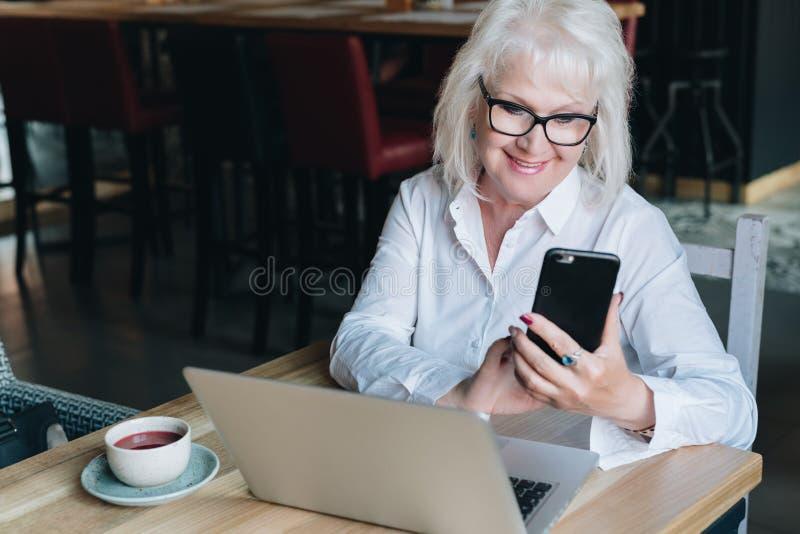 La empresaria sonriente vestida en la camisa blanca se está sentando en la tabla delante del ordenador portátil y de usar smartph fotografía de archivo libre de regalías