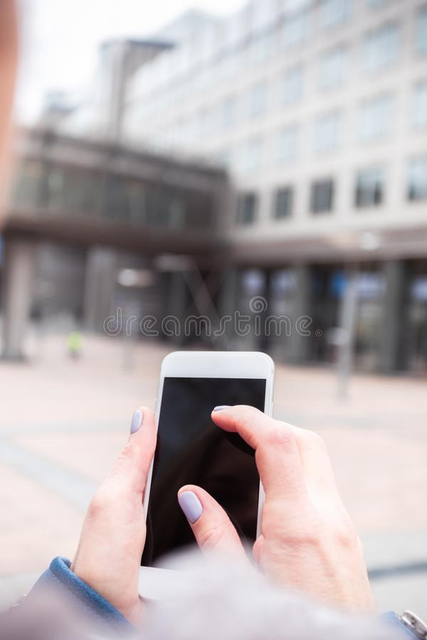 La empresaria utiliza un teléfono móvil en la calle contra un edificio de oficinas imagenes de archivo