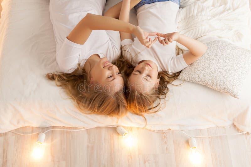 La endecha de la madre y de la hija en la cama y hace el corazón por las manos Visión desde arriba togetherness Interior del desv imagen de archivo libre de regalías