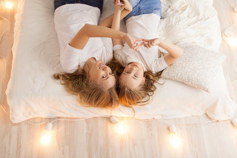 La endecha de la madre y de la hija en la cama y hace el corazón por las manos Visión desde arriba togetherness Interior del desv foto de archivo libre de regalías