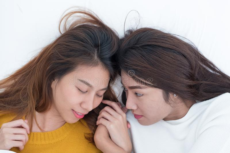 La endecha lesbiana de los pares de Asia LGBT en cama y el cierre observan con felicidad imagen de archivo libre de regalías