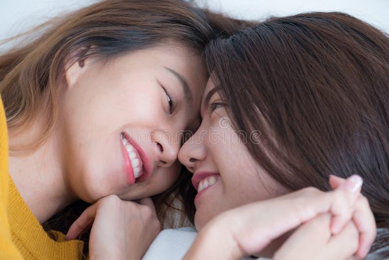 La endecha lesbiana de los pares de Asia LGBT en cama y el cierre observan con felicidad fotos de archivo