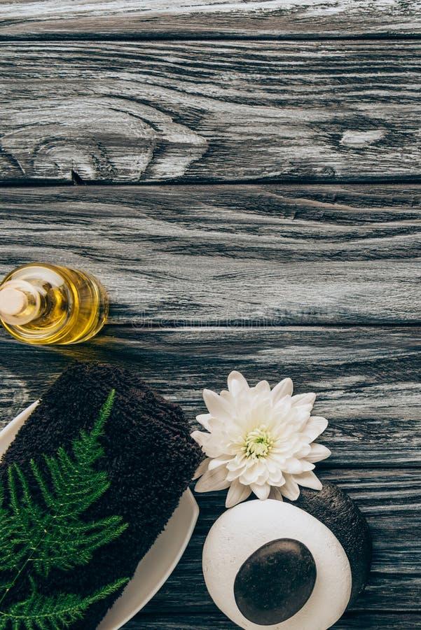 la endecha plana con el balneario y el arreglo del tratamiento del masaje con aceite, la toalla, los guijarros y el crisantemo fl imágenes de archivo libres de regalías