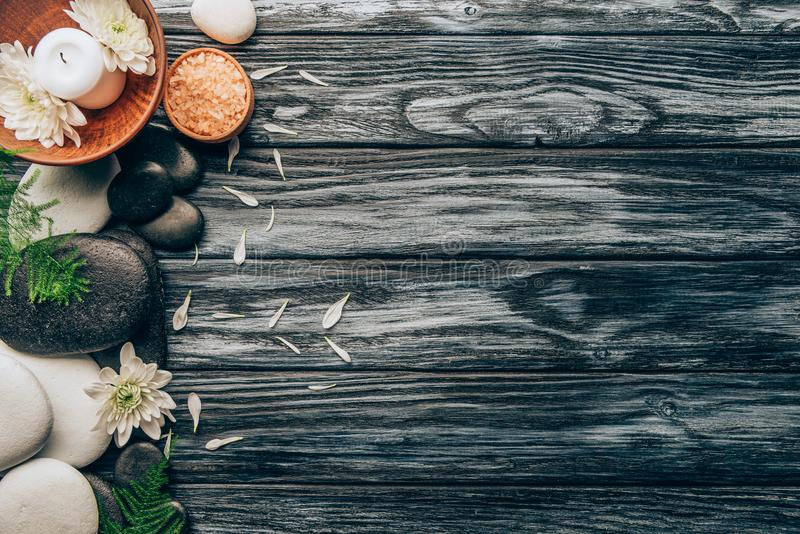 la endecha plana con el balneario y el arreglo del tratamiento del masaje con los guijarros, la sal y el crisantemo florece fotografía de archivo libre de regalías
