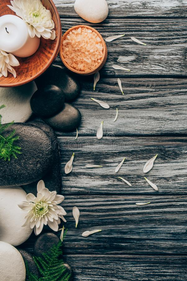 la endecha plana con el balneario y el arreglo del tratamiento del masaje con los guijarros, la sal y el crisantemo florece imagen de archivo