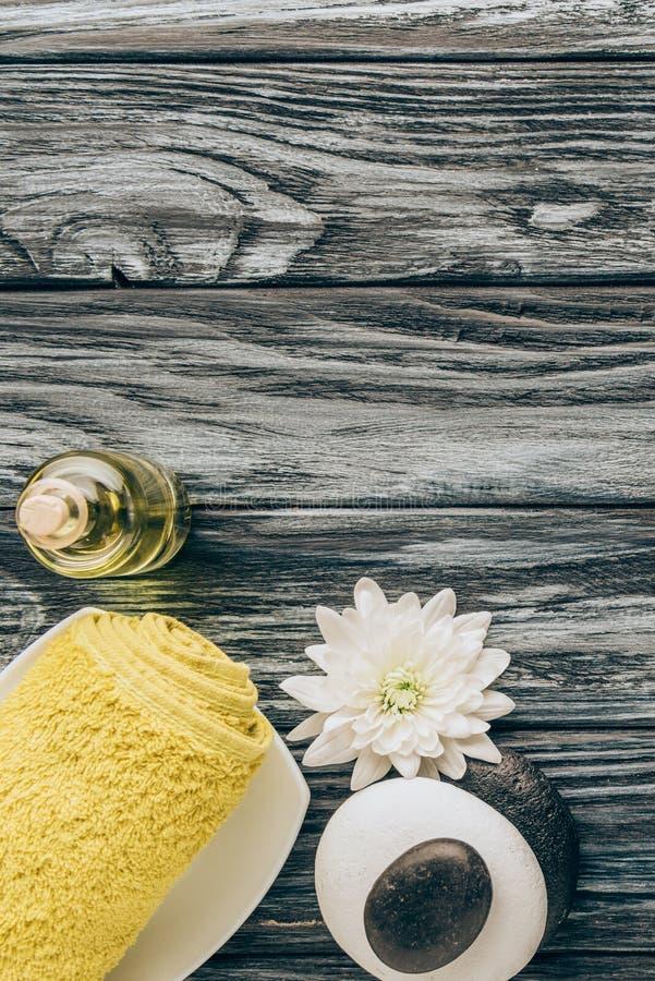 la endecha plana con el balneario y el arreglo del tratamiento del masaje con la toalla, el aceite esencial, los guijarros y el c foto de archivo