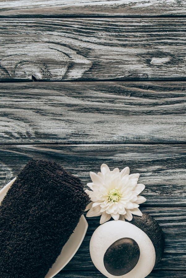 la endecha plana con el balneario y el arreglo del tratamiento del masaje con la toalla, los guijarros y el crisantemo florecen imagenes de archivo
