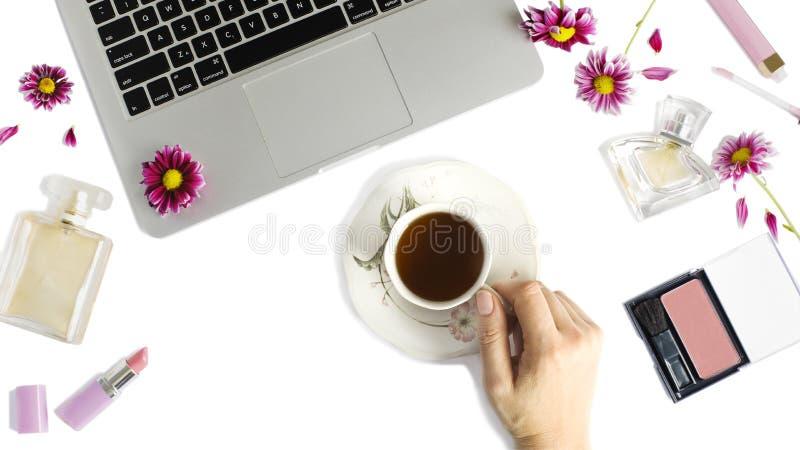 La endecha plana con el ordenador portátil, taza del té, botellas de perfume, mujer hace u [los productos y las flores fotografía de archivo libre de regalías