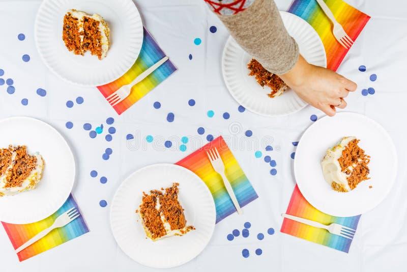 La endecha plana con la torta de cumpleaños junta las piezas en las placas del Libro Blanco Birthd fotos de archivo