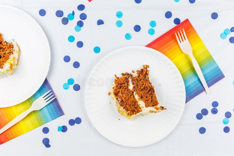 La endecha plana con la torta de cumpleaños junta las piezas en las placas del Libro Blanco Birthd fotos de archivo libres de regalías