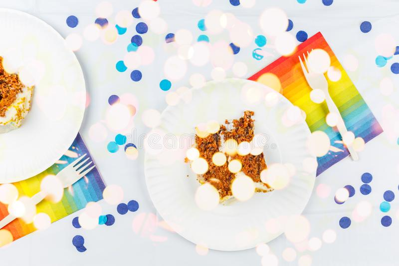 La endecha plana con la torta de cumpleaños junta las piezas en las placas del Libro Blanco Concepto de la celebración de la fies foto de archivo libre de regalías