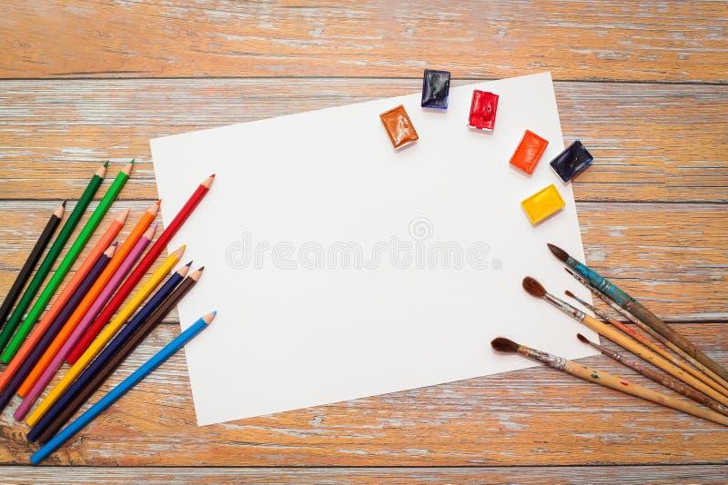 La endecha plana del Libro Blanco, las acuarelas, la brocha y el color dibujaron a lápiz en la tabla de madera imágenes de archivo libres de regalías