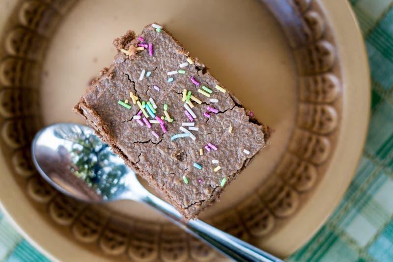 La endecha plana sobre la torta de chocolate con colorido asperja con el foco selectivo imagen de archivo