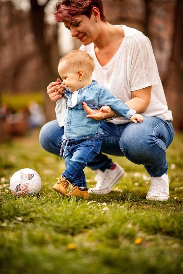 La energía feliz de la niñez, bebé de la actividad con su madre juega foto de archivo