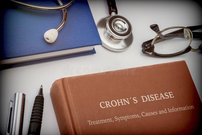 La enfermedad de Crohn titulado del libro junto con el equipamiento médico imagen de archivo libre de regalías
