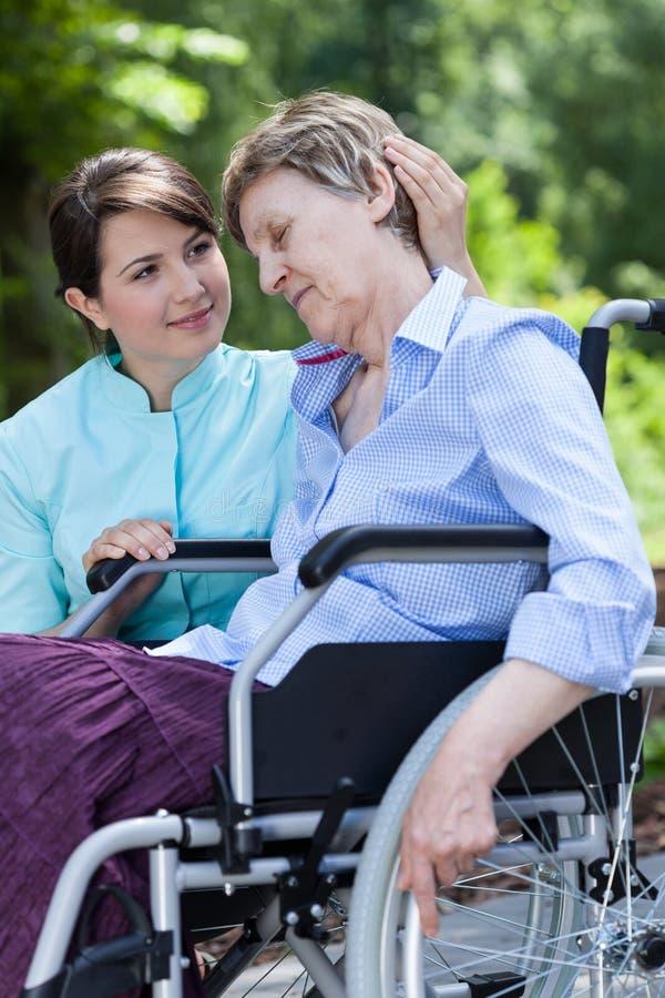 La enfermera abraza a una mujer discapacitada mayor imagen de archivo libre de regalías