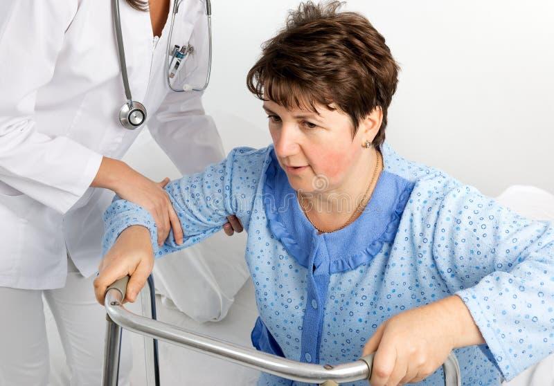 La enfermera ayuda a un paciente a levantarse imagen de archivo libre de regalías