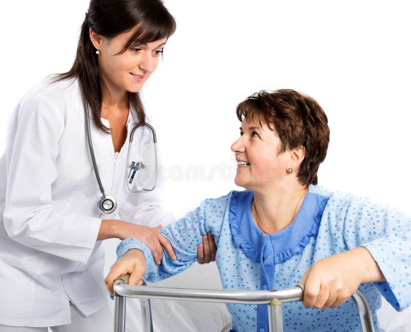 La enfermera ayuda a un paciente mayor a levantarse foto de archivo libre de regalías