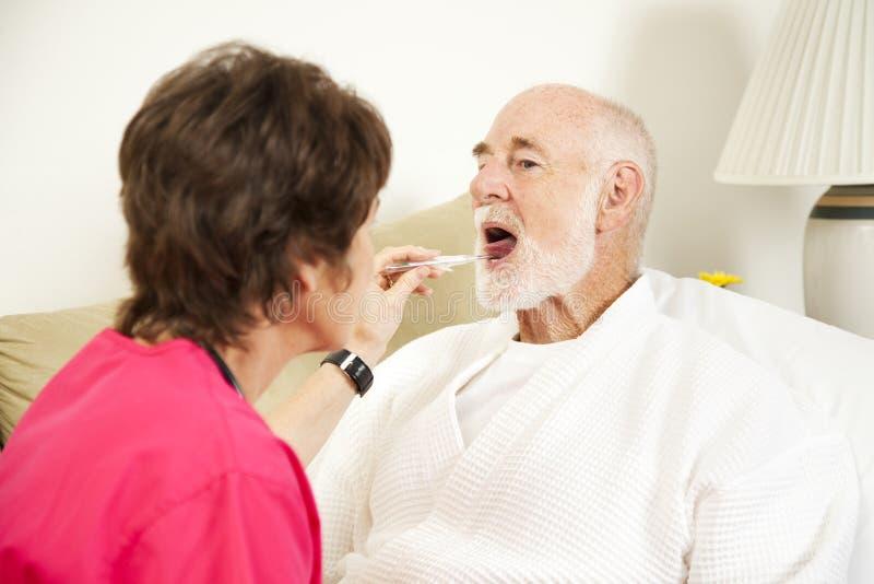 La enfermera casera toma temperatura fotografía de archivo