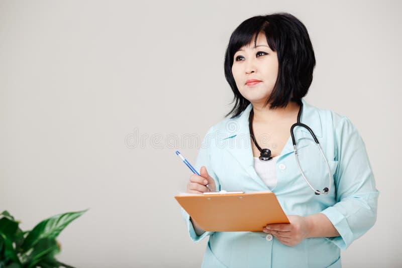 La enfermera de sexo femenino Curvy se coloca todavía escribe los resultados por la pluma en el papel, en capa del laboratorio mé fotos de archivo libres de regalías