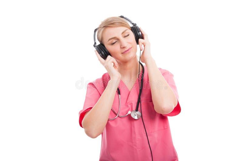 La enfermera de sexo femenino que escuchaba las auriculares con los ojos se cerró foto de archivo libre de regalías