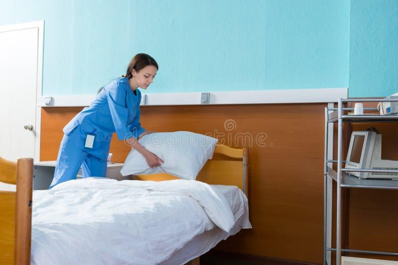 La enfermera de sexo femenino sostiene una almohada blanca sobre la cama de hospital en el h imagenes de archivo