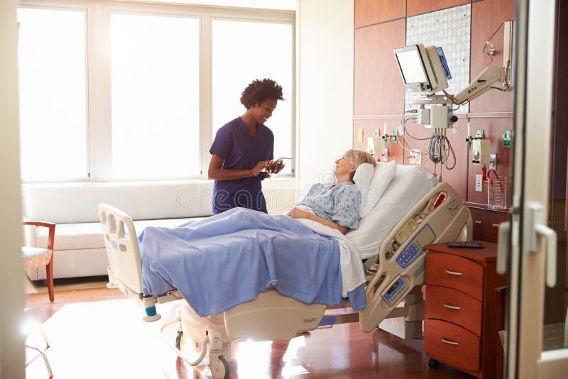 La enfermera With Digital Tablet del hospital habla con el paciente mayor foto de archivo libre de regalías