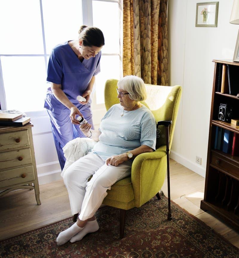 La enfermera está tomando cuidado de una mujer mayor fotografía de archivo libre de regalías