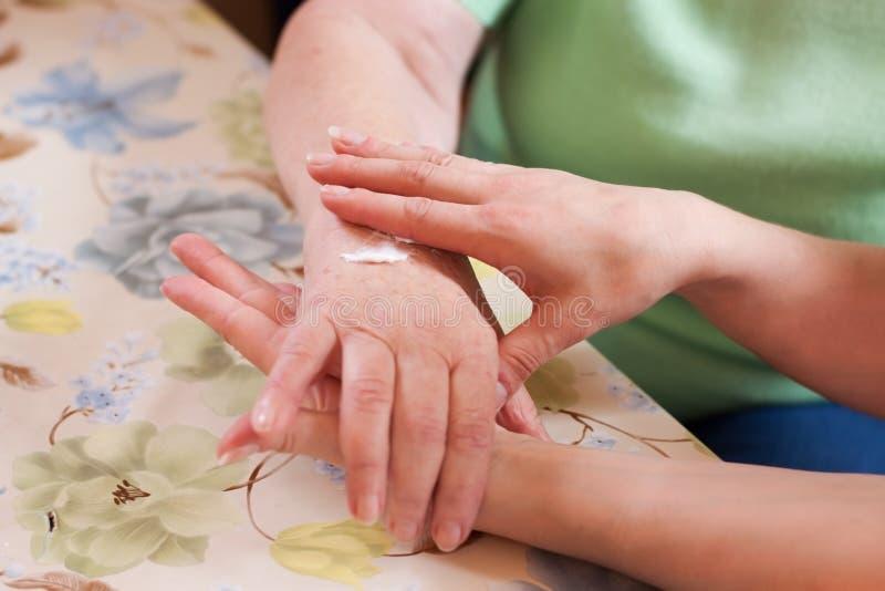 La enfermera geriátrica unta la mano mayor de los womans fotos de archivo libres de regalías