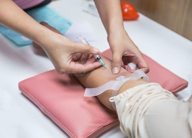 La enfermera inyecta la aguja en la muestra de sangre paciente del dibujo del brazo fotografía de archivo