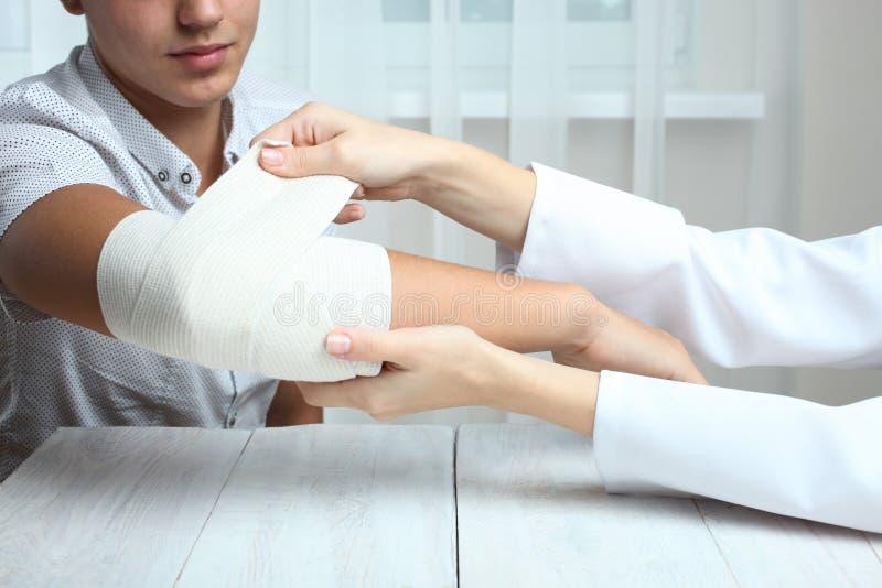 La enfermera muele el codo del ` s del muchacho con el vendaje elástico fotos de archivo libres de regalías