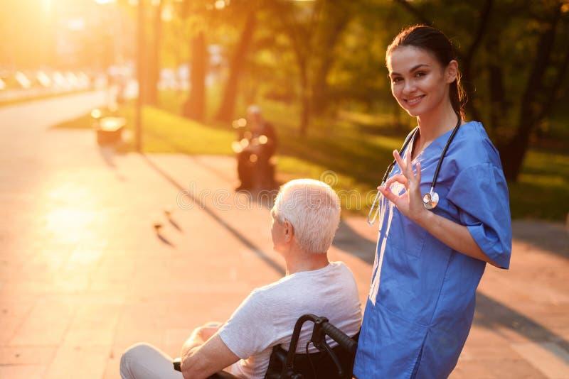 La enfermera muestra el gesto todo MUY BIEN Detrás de ella es un viejo hombre en una silla de ruedas imagen de archivo libre de regalías