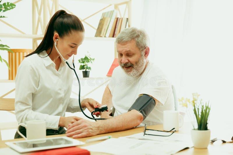 La enfermera que visita que toma cuidado del hombre mayor imagen de archivo