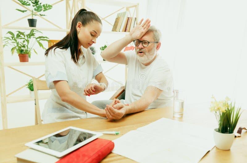 La enfermera que visita que toma cuidado del hombre mayor foto de archivo