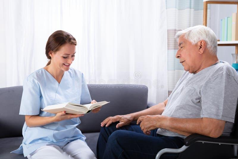 La enfermera Reading Book For inhabilit? al hombre mayor fotos de archivo libres de regalías