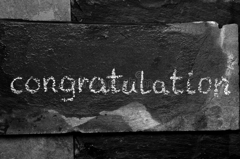 La enhorabuena de la palabra escrita con tiza en piedra negra imagen de archivo libre de regalías