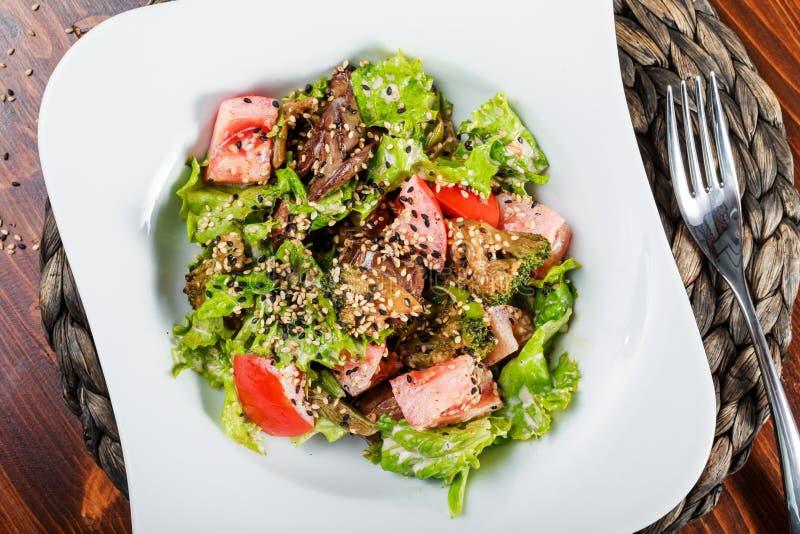 La ensalada caliente con el hígado de pollo, tomates, lechuga se va, bróculi en la tabla de madera Alimento sano imágenes de archivo libres de regalías