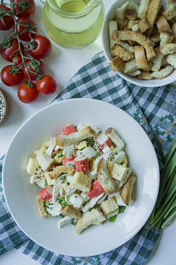 La ensalada con las galletas, los palillos del cangrejo, el prendedero del pollo, las hierbas frescas y el queso duro sazonados c foto de archivo libre de regalías