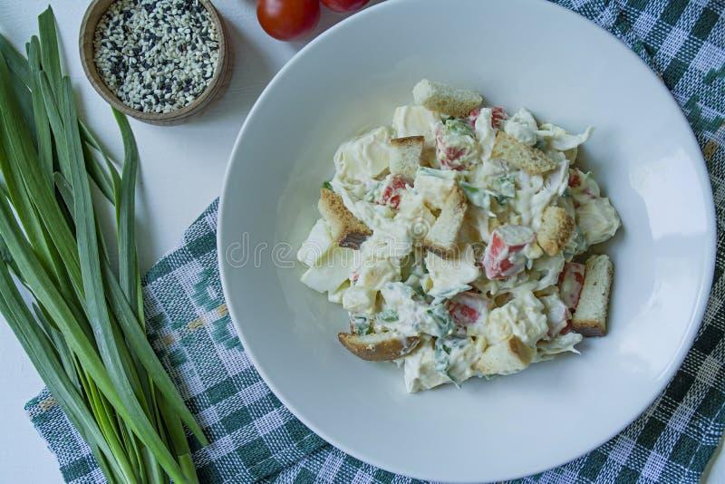 La ensalada con las galletas, los palillos del cangrejo, el prendedero del pollo, las hierbas frescas y el queso duro sazonados c fotografía de archivo