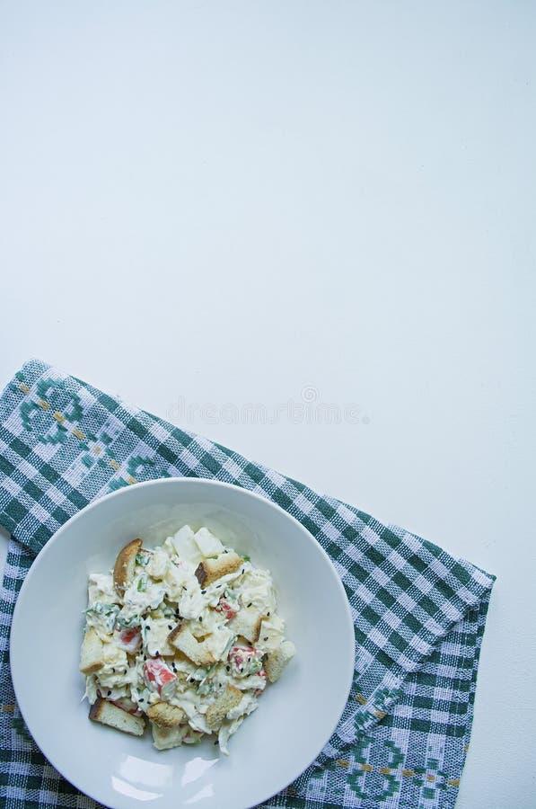 La ensalada con las galletas, los palillos del cangrejo, el prendedero del pollo, verdes frescos y el queso duro, sazonados con a fotografía de archivo