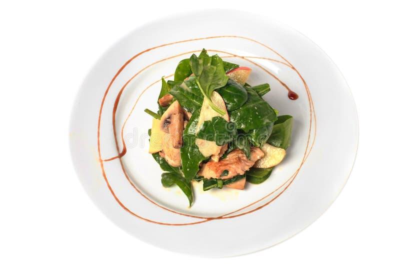 La ensalada de la espinaca en placa redonda con la pera, chiken, las setas y salsa Visión superior Aislado en blanco imagen de archivo