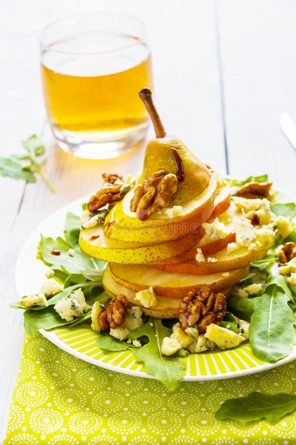 La ensalada de fruta, pera entera cortada, nueces caramelized en miel, queso verde y arugula imagen de archivo