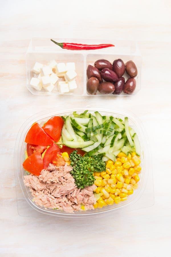 La ensalada sana con el atún y las verduras en el envase de plástico para la dieta almuerzan en el fondo de madera blanco imagen de archivo