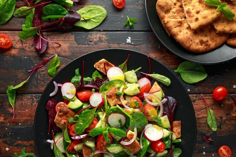 La ensalada tradicional del fattoush en una placa con los cuscurrones de la pita, pepino, tomate, cebolla roja, verduras se mezcl imagenes de archivo