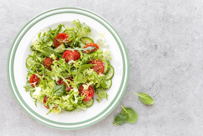 La ensalada vegetal sana del tomate fresco, pepino, espinaca, frize y sésamo en la placa Menú de la dieta fotos de archivo