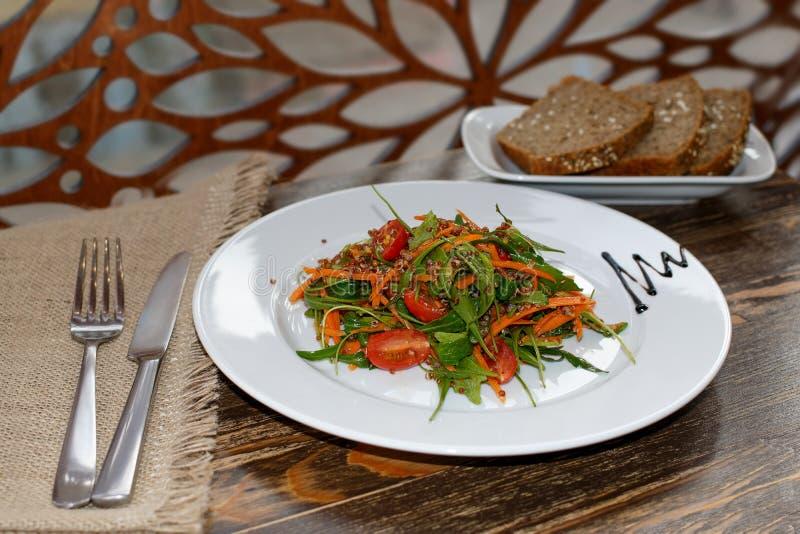 La ensalada vegetariana con las verduras, el arugula y el pan brotado del quinoa y ácimo foto de archivo
